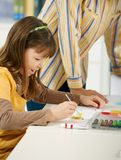 Schoolgirl painting in art class. Elemantary age girl sitting at desk enjoying painting with colors in art class at primary school classroom, smiling Royalty Free Stock Image