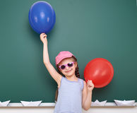 Schoolgirl with paper boat and balloon play near a blackboard, empty space, education concept Royalty Free Stock Photography
