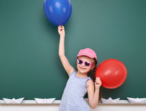 Schoolgirl with paper boat and balloon play near a blackboard, empty space, education concept Stock Image