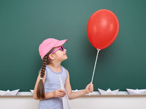 Schoolgirl with paper plane and balloon play near a blackboard, empty space, education concept Royalty Free Stock Images