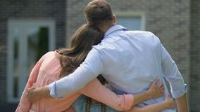 Schoolgirl and parents hugging together looking new house, mortgage, back view. Stock footage stock video