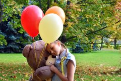 girl with big teddy bear and balloons in the park.  Problems teenagers at school