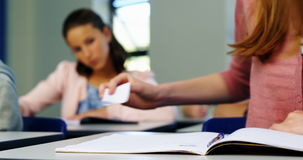 Schoolgirl passing chit to her classmate during exam in classroom. At school stock video footage