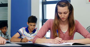 Schoolgirl passing chit to her classmate during exam in classroom. At school stock footage
