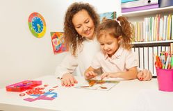 Schoolgirl pieces together a jigsaw puzzle. With her teacher at the classroom desk Royalty Free Stock Photos