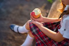 Schoolgirl in uniform is eating an apple in the park. stock photo