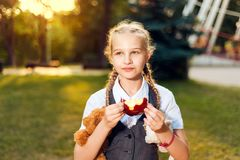 Schoolgirl with pigtails in uniform is eating an apple in the park stock photos