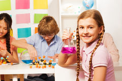 Schoolgirl with plaits holding flask at school lab. Cute schoolgirl with long plaits holding flask with pink reagent at the school laboratory Stock Images