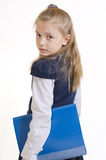 The schoolgirl with the plastic folder. The girl of 9 years in a school uniform with the blue plastic folder for documents poses in studio stock photography