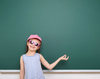 Schoolgirl play near a blackboard. Holds something in her hands. Empty space. Education concept. Stock Images
