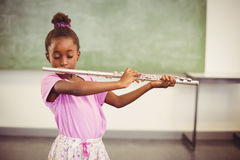 Schoolgirl playing flute in classroom Royalty Free Stock Images