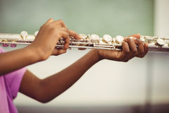 Schoolgirl playing flute in classroom Royalty Free Stock Photo