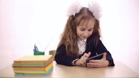 Schoolgirl playing games on a mobile phone stock video footage