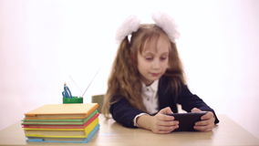 Schoolgirl playing games on a mobile phone stock footage