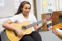 Schoolgirl playing guitar in music class Royalty Free Stock Image