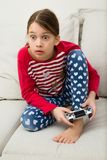 Girl Plays Videogame. A schoolgirl plays a videogame with a game controller, showing surprise and excitement Stock Images