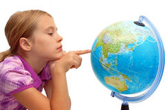 Schoolgirl pointing at globe stock photo