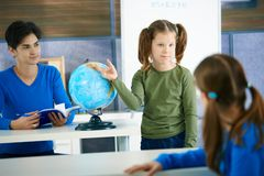 Schoolgirl pointing at globe Stock Image