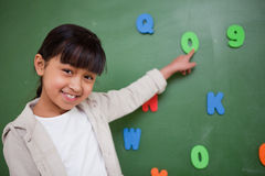 Schoolgirl pointing at a letter Stock Photo