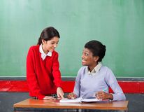 Schoolgirl Pointing On Paper While Teacher Looking Stock Photos