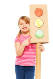 Schoolgirl pointing to green light of signal. Close-up picture of smiling girl, pointing to the green light of handmade cardboard light-signal, isolated on white Stock Photo