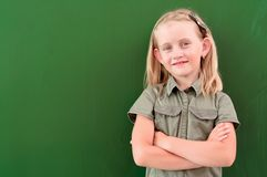 Schoolgirl portrait near the blackboards. Looking at the camera royalty free stock image