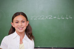 Schoolgirl posing in front of a chalkboard Stock Images