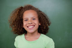 Schoolgirl posing in front of an empty chalkboard Stock Photo