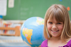 Schoolgirl posing in front of a globe Stock Photos