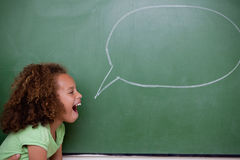 Schoolgirl posing with a speech bubble. In a classroom Stock Images