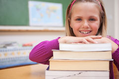 Schoolgirl posing with a stack of books Royalty Free Stock Photography