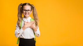Schoolgirl Pressing Hands To Chest Expressing Gratitude On Yellow Background