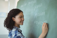 Schoolgirl pretending to be a teacher in classroom Royalty Free Stock Image