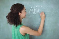 Schoolgirl pretending to be a teacher in classroom Stock Image