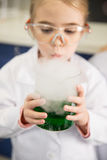 Schoolgirl in protective goggles holding flask with chemical sample Royalty Free Stock Images