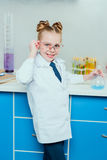 Schoolgirl in protective goggles and white coat holding flask with reagent Royalty Free Stock Photography