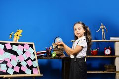Schoolgirl with proud face holds little globe in her hands royalty free stock photo
