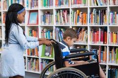 Schoolgirl pushing a boy on wheelchair Royalty Free Stock Photos