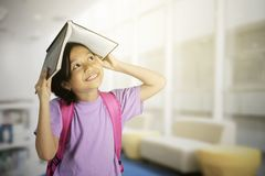 Schoolgirl puts an open book on her head Royalty Free Stock Photos