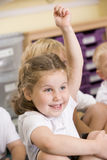 A schoolgirl raises her hand in a primary class Stock Photos