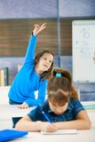 Schoolgirl raising hand. Schoolgirl in focus standing up in back row of class raising hand to answer question Royalty Free Stock Photos