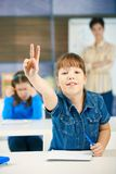 Schoolgirl raising hand. To answer question smiling, other girl and teacher in background of class Royalty Free Stock Photos