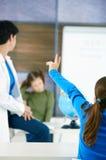 Schoolgirl raising hand Stock Image