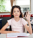 Schoolgirl Raising Hand In Classroom Stock Photos