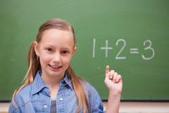 Schoolgirl raising her hand Stock Image