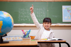 Schoolgirl raising her hand to answer a question. Smiling schoolgirl raising her hand to answer a question in a classroom stock photography