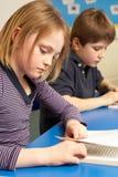 Schoolgirl Reading Book In Classroom Stock Images
