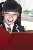 Schoolgirl reading a book with her face lit up Royalty Free Stock Images