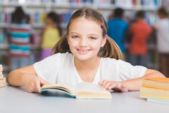 Schoolgirl reading book in library Stock Photography