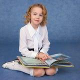 Schoolgirl reading book sitting on floor Stock Photo